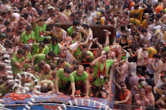 kds Revellers on a truck throw tomatoes into the crowd during the annual